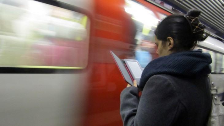 Moça lê um Kindle enquanto espera o trem do metrô.