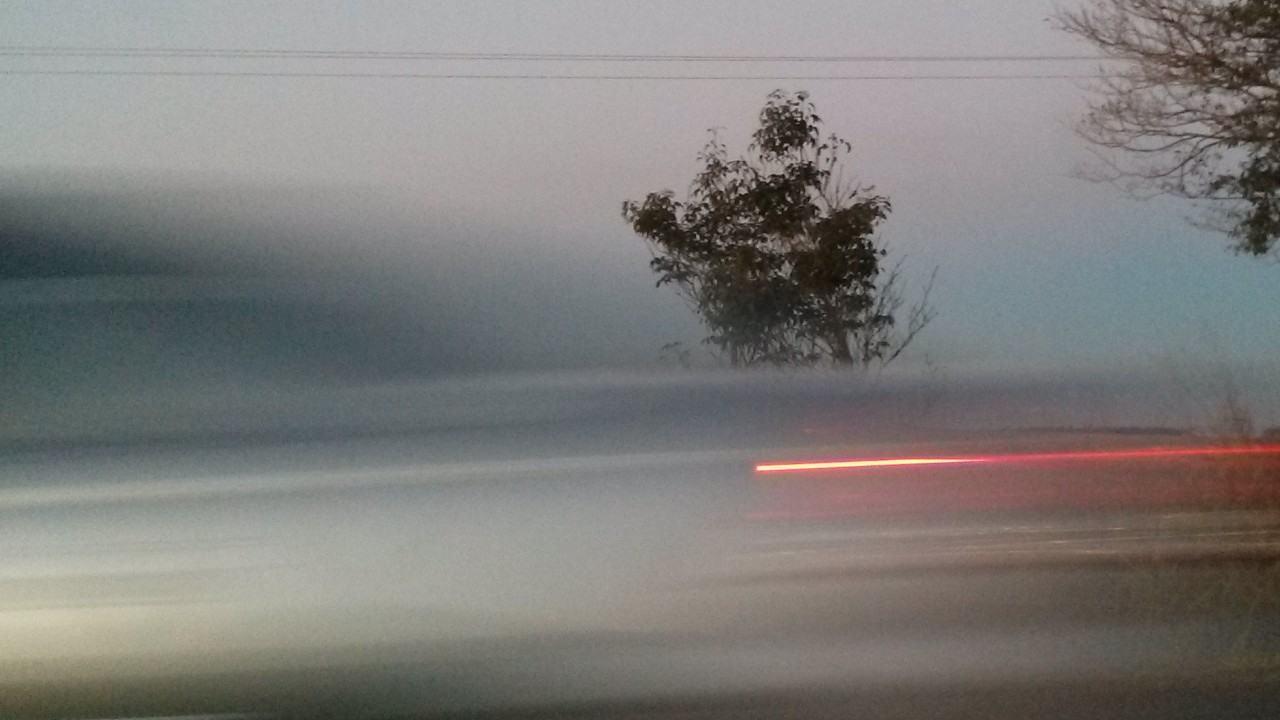 Foto de um carro passando rápido na estrada.
