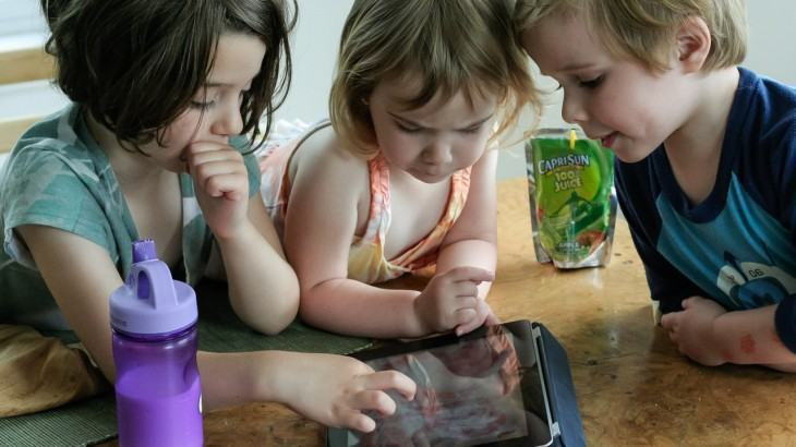Três crianças brincando em um tablet.