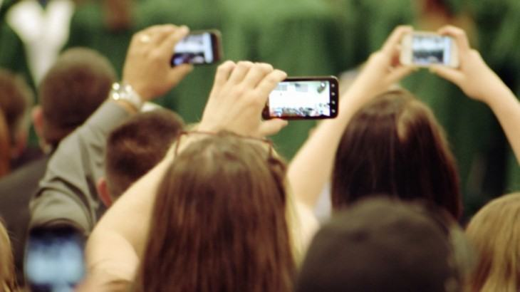 Várias pessoas tirando fotos com celulares.