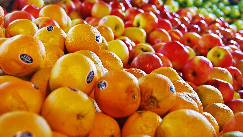 Uma simpática banca de laranjas e maçãs.