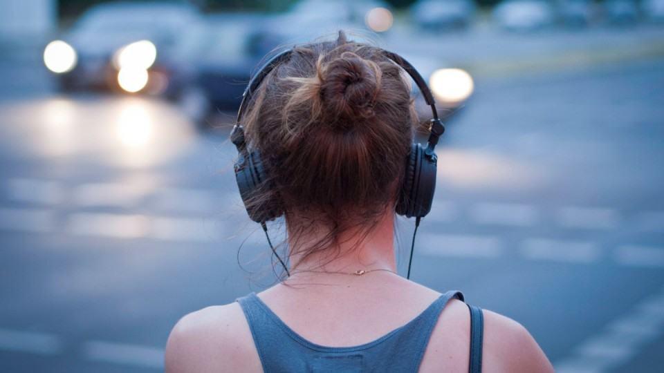 Moça na rua com headphones.