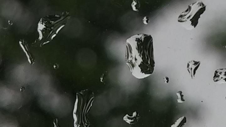 Detalhe de gotas d'água focadas contra a janela.