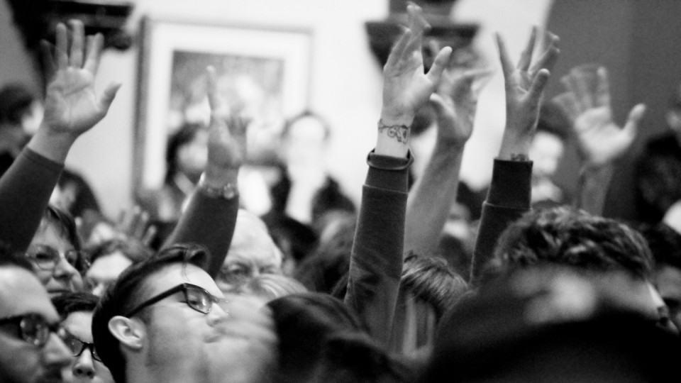 Pessoas com as mãos levantadas.