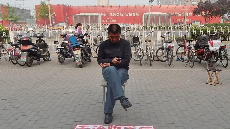 Senhor chinês mexendo no celular.