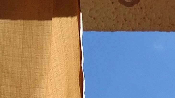 Uma cortina e o céu azul.