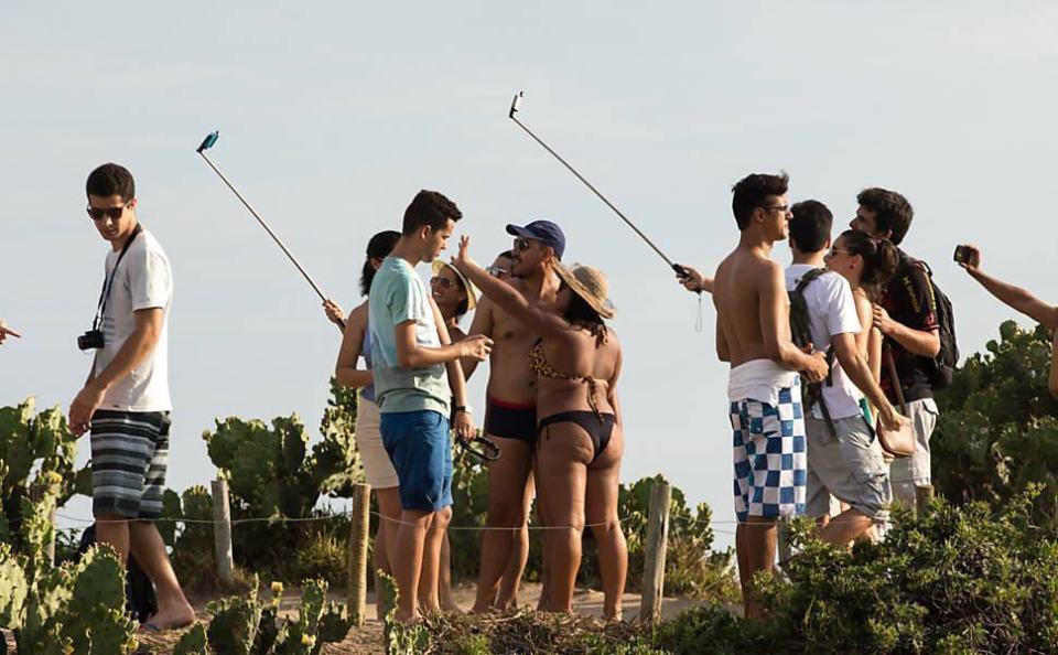 Turistas e cariocas brincando com pau de selfie.