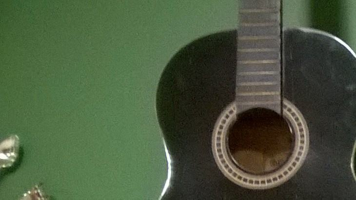 Um violão numa parede verde.