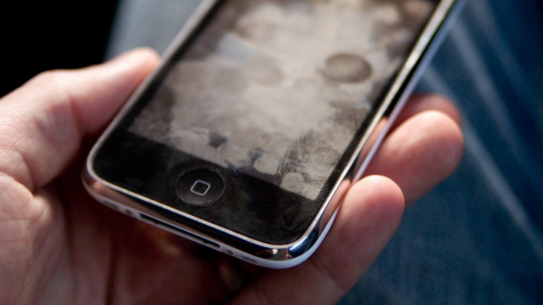 Tela de iPhone antigo cheia de marcas de dedos.