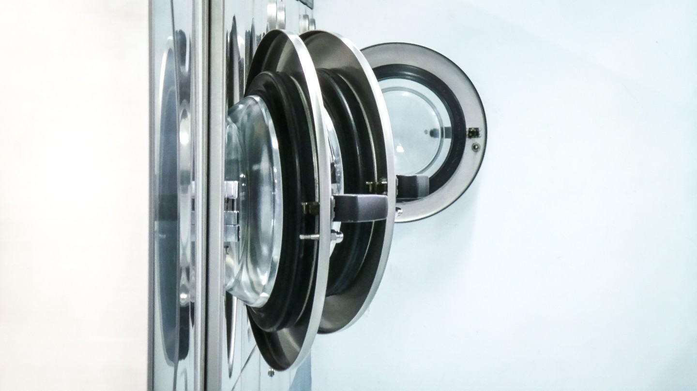 Tampas de máquinas de lavar roupa abertas.