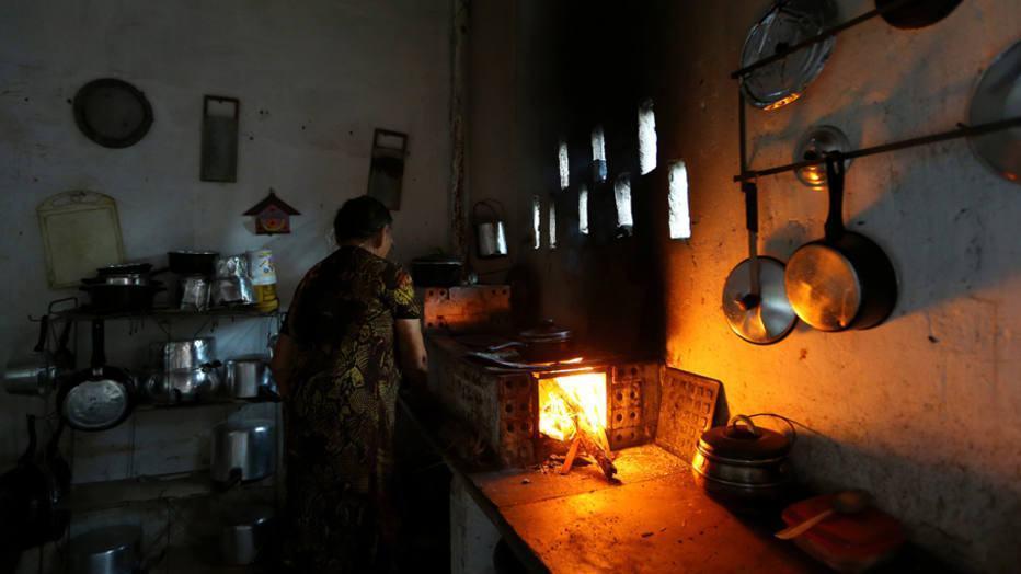 Senhora cozinha em seu fogão a lenha.