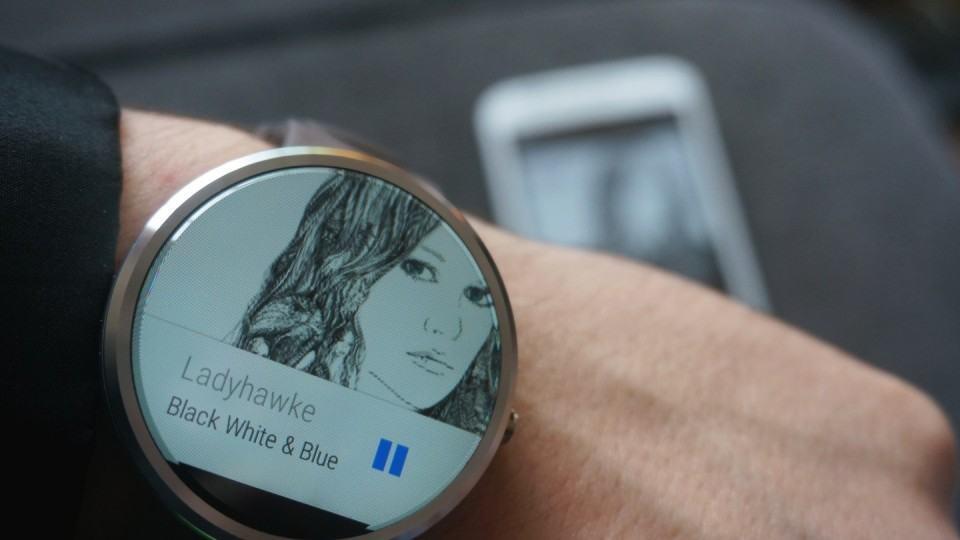 À frente, Moto 360. Atrás, smartphone onde a música está tocando.