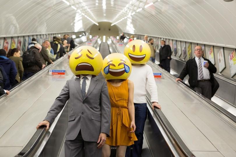 Três pessoas com cabeças de emoji descendo escadas no metrô de Londres.