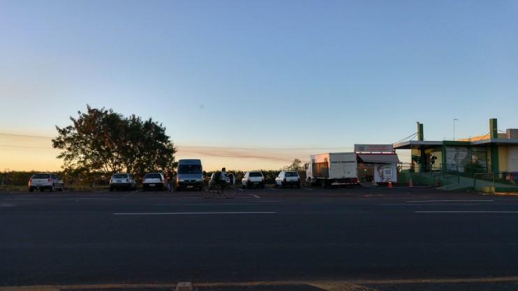 Carros enfileirados no pôr do Sol.