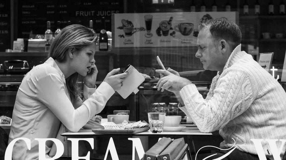Casal mexendo no celular enquanto toma café.