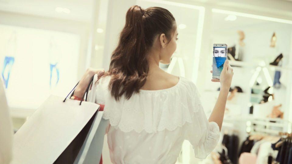 Mulher fazendo pagamento pelo leitor de íris do Galaxy Note 7.