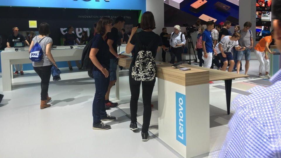 Visitantes mexem em smartphone da Lenovo.