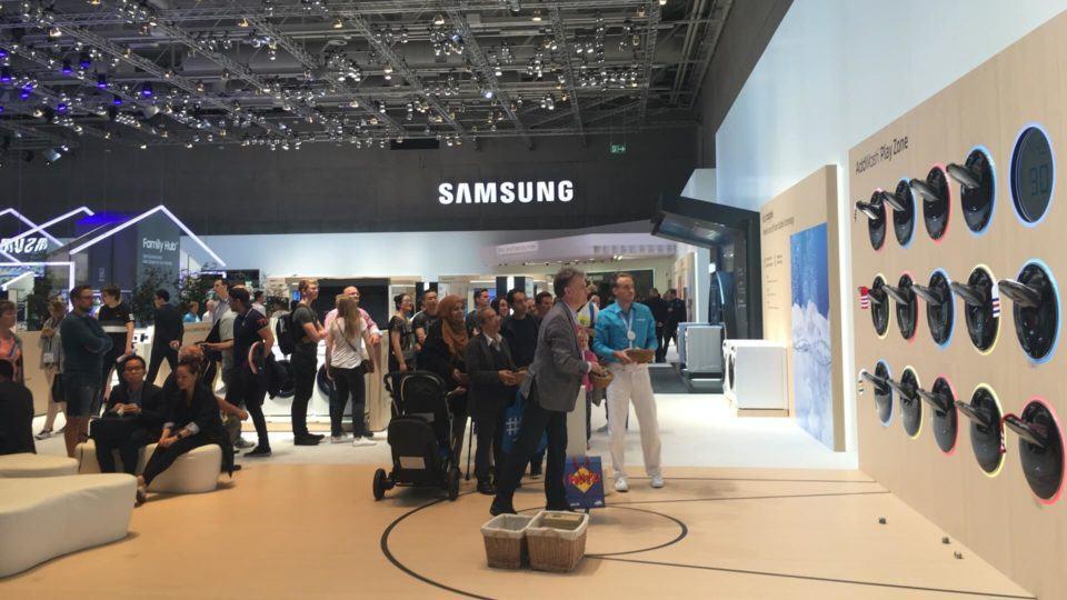 Pessoas comuns na IFA em torno de um game no estande da Samsung.