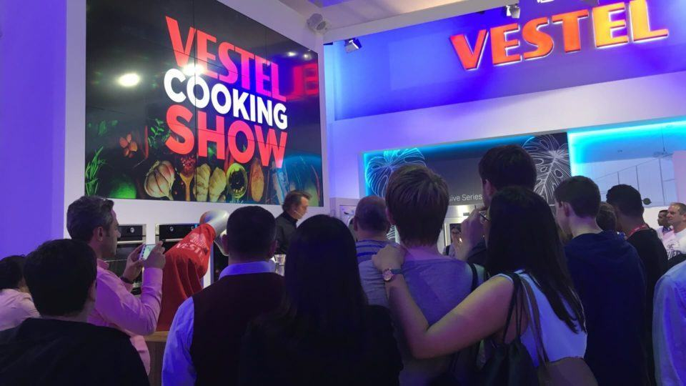 Visitantes reunidos em torno de um show de culinária.