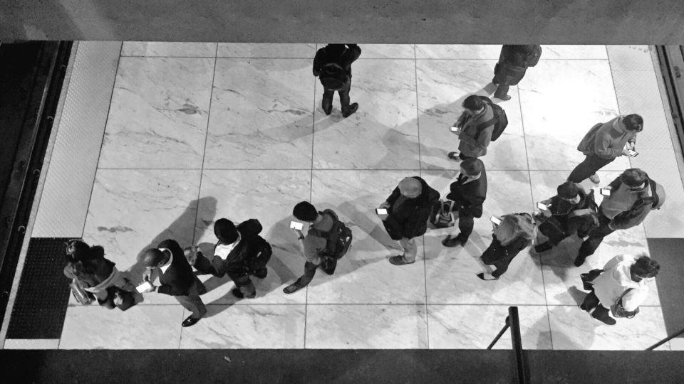 Pessoas em fila olhando para seus smartphones.