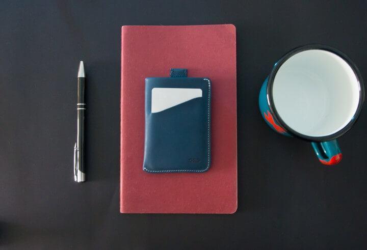 Carteira da Chimp sobre uma mesa ao lado de caneta e caneca.
