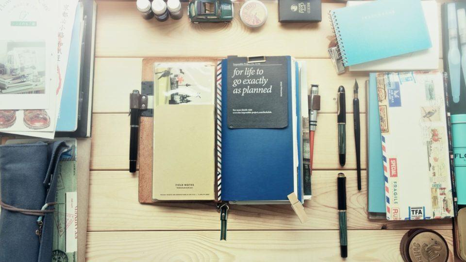 Caderno de notas em cima de uma mesa cheia de objetos.