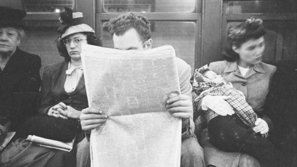 Homem lê jornal sentado em trem do metrô de Nova York.