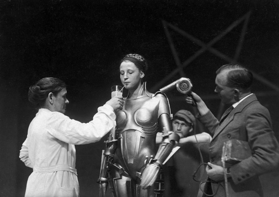 Brigitte Helm é amparada durante a filmagem da cena em que encarna a robô.
