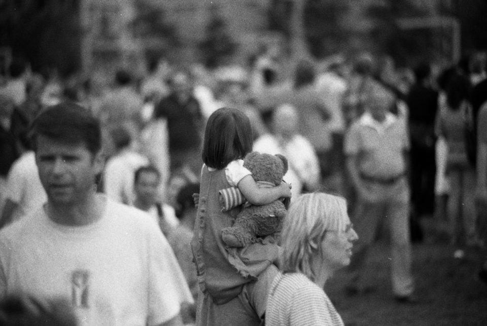 Criança segurando ursinho no meio da multidão.