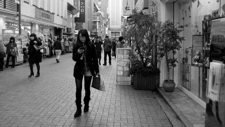 Mulher andando com smartphone na mão.