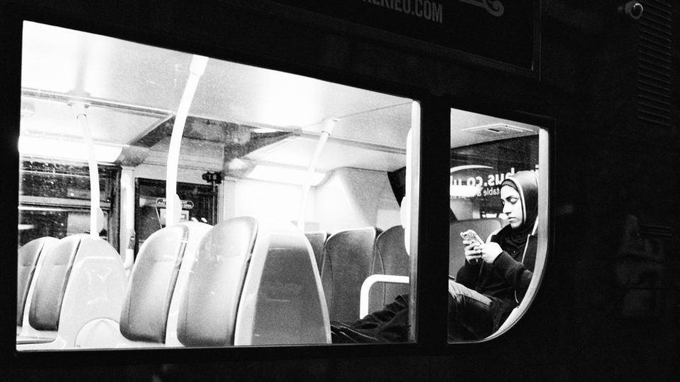 Mulher usando smartphone no ônibus.