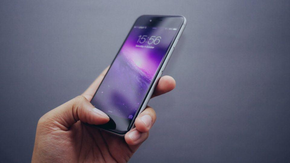Mão segurando um iPhone com o polegar sobre o sensor de digitais.