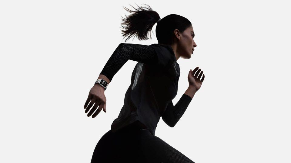 Mulher correndo com um Apple Watch no pulso.