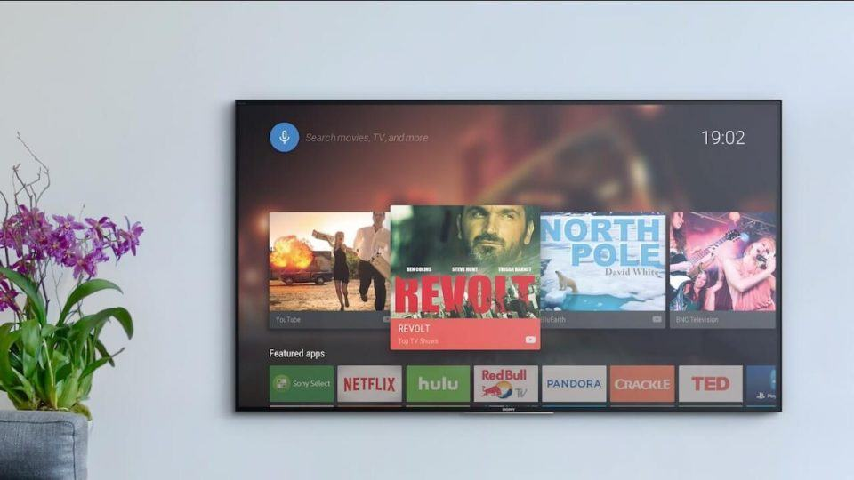 Smart TV com Android TV pendurada na parede.