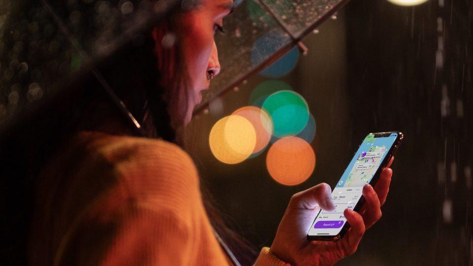 Mulher mexe em um iPhone Xs debaixo de chuva.