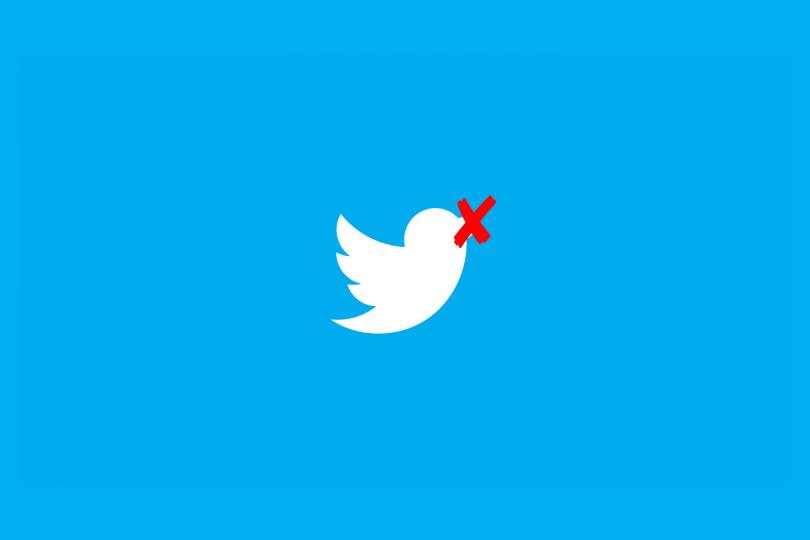 Pássaro logo do Twitter com um X vermelho no bico.