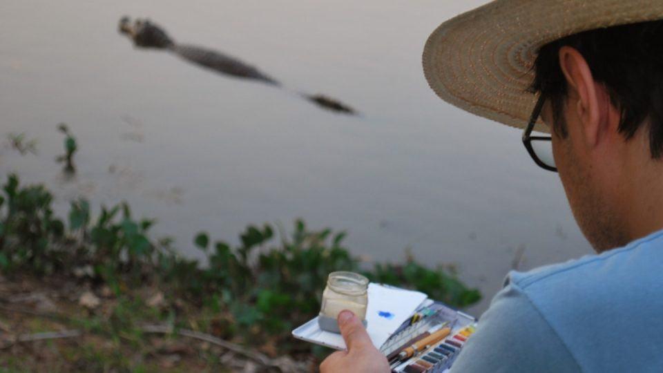 Diogo desenhando à beira de um rio com um jacaré passando ao fundo.