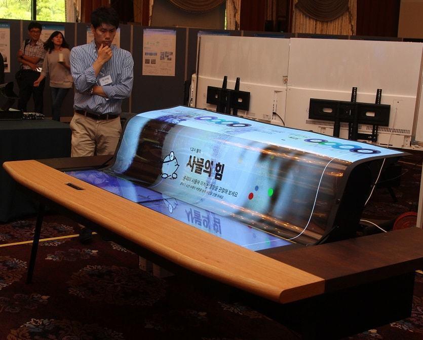 Homem observa tela flexível da LG em uma mesa com dois níveis.