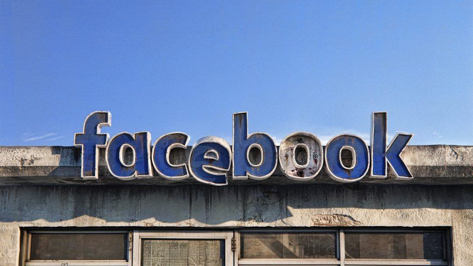 Renderização mostrando uma fachada fictícia do Facebook em estado decadente, enferrujada e com letras faltando.