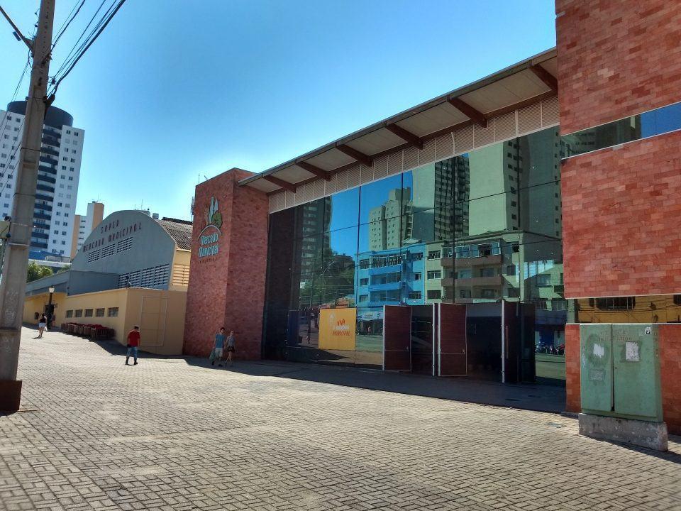 Foto da fachada do Mercado Municipal de Curitiba em um dia ensolarado.
