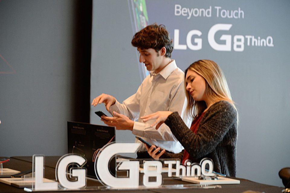 Pessoas mexendo as mãos em frente ao celular da LG para desbloqueá-lo.