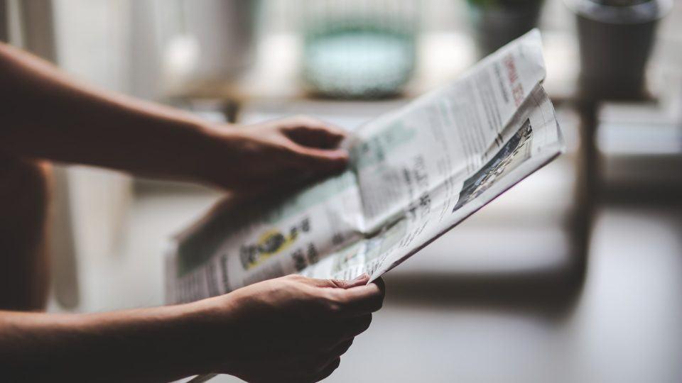 Pessoa lendo jornal em papel.