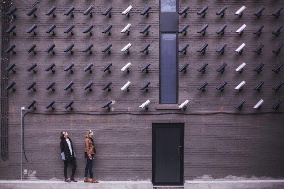 Duas pessoas olhando para uma parede repleta de câmeras de vigilância.