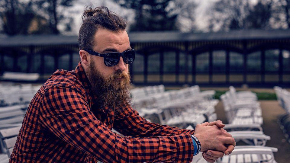 Homem de barba comprida, óculos escuros e camisa xadrez sentado.