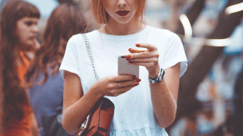 Mulher em uma festa olha o celular com outras pessoas ao fundo.