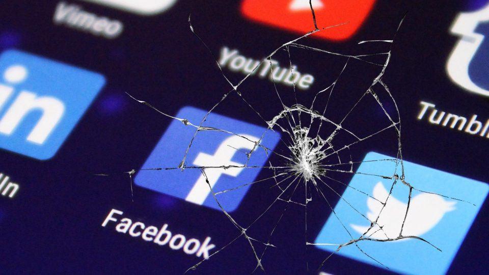 Ícones de redes sociais vistos através de uma tela trincada.