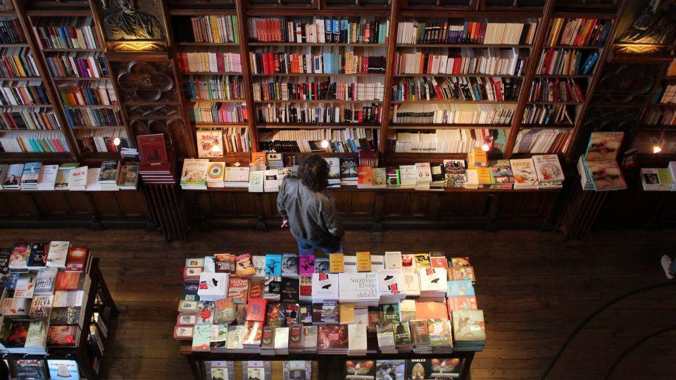 Homem entre prateleiras de uma livraria.