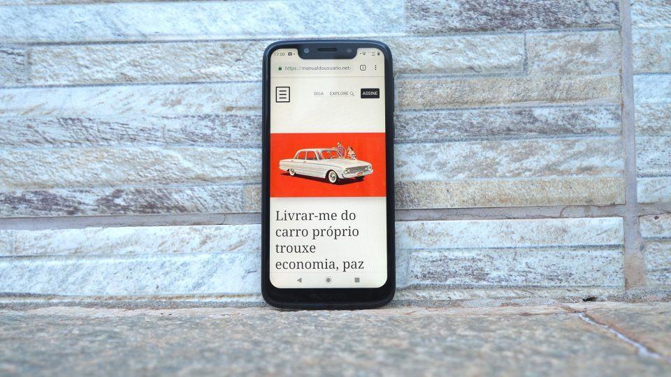 Moto G7 Play com Manual do Usuário aberto.