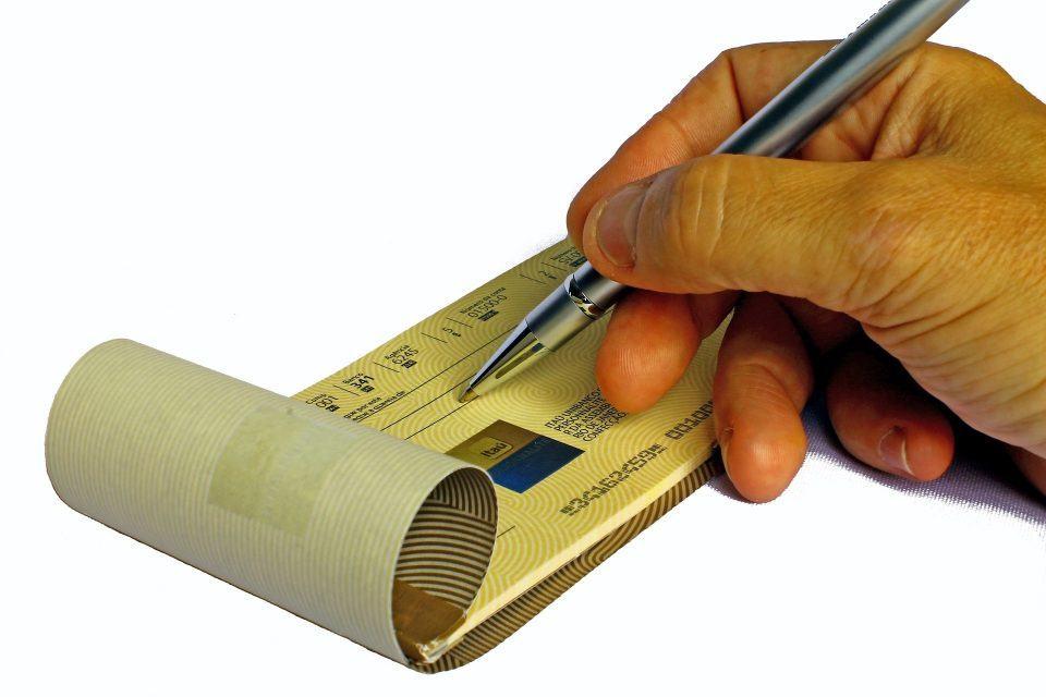 Mão preenchendo um cheque do Itaú.