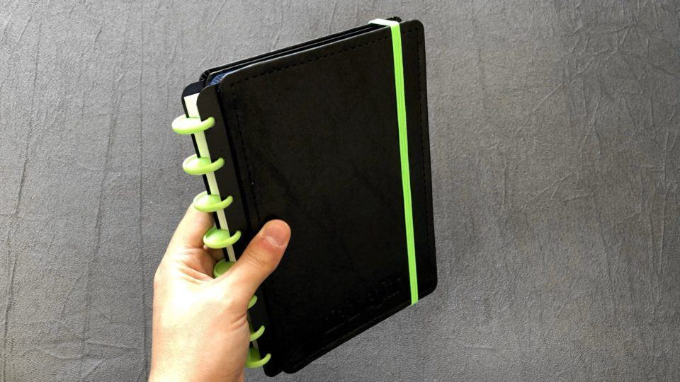 Mão segurando um caderno inteligente médio.